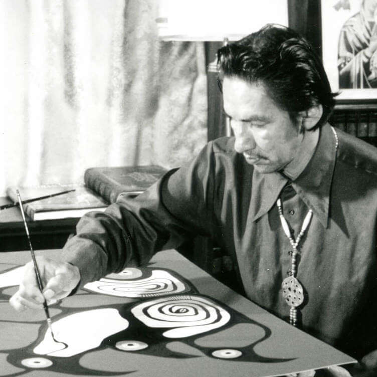 <p>Norval Morrisseau painting in his home in 1973 for the filming of the NFB documentary Paradox of Norval Morrisseau. Morrisseau did not have access to an artist-studio space.</p> <p></p> <p>Banner:Norval Morrisseau, <em>Artist and Shaman between Two Worlds</em>, 1980, acrylic on canvas, 175 x 282 cm, National Gallery of Canada, Ottawa.</p>