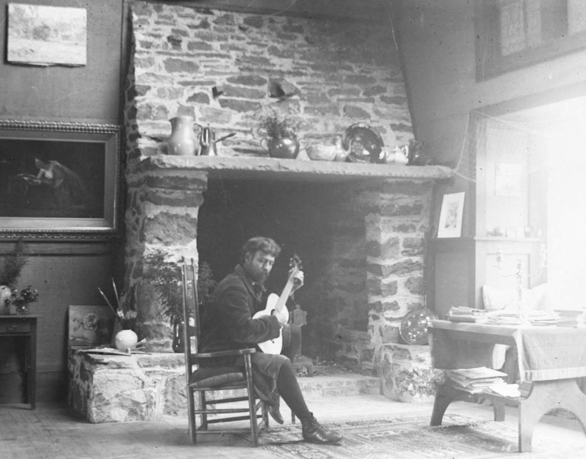 George Agnew Reid playing guitar in front of the studio fireplace, Onteora, New York, c.1893